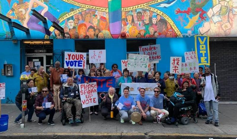 A multi-racial group gather with voting signs