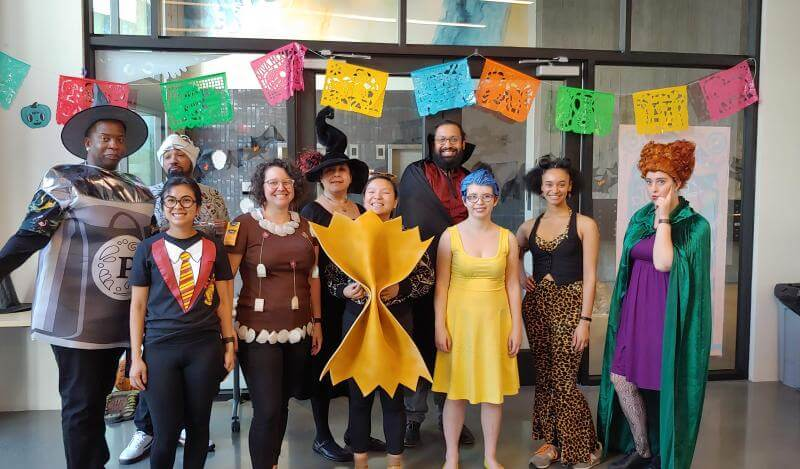 A multi-racial group of people in Halloween costumes pose