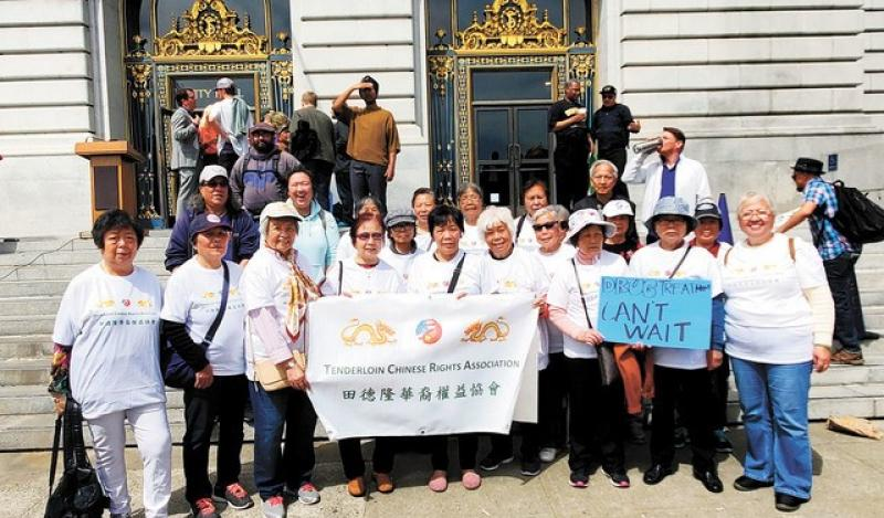 A group of people stand outside City Hall with a Chinese Rights Association sign