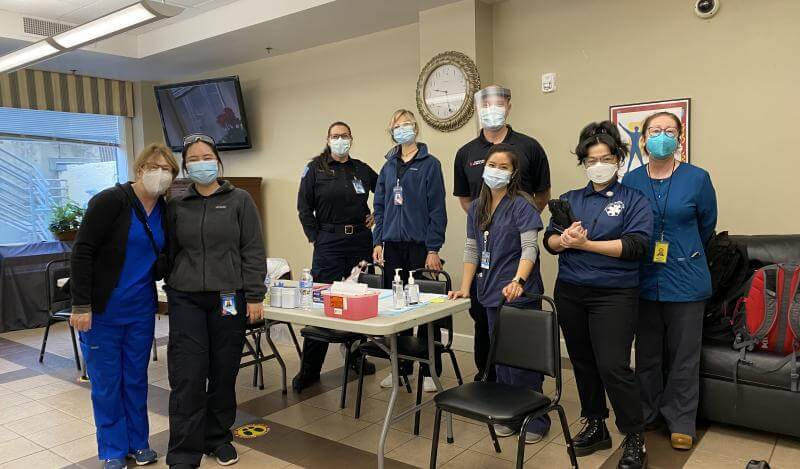 A group of staff from the Department of Public Health pose in masks