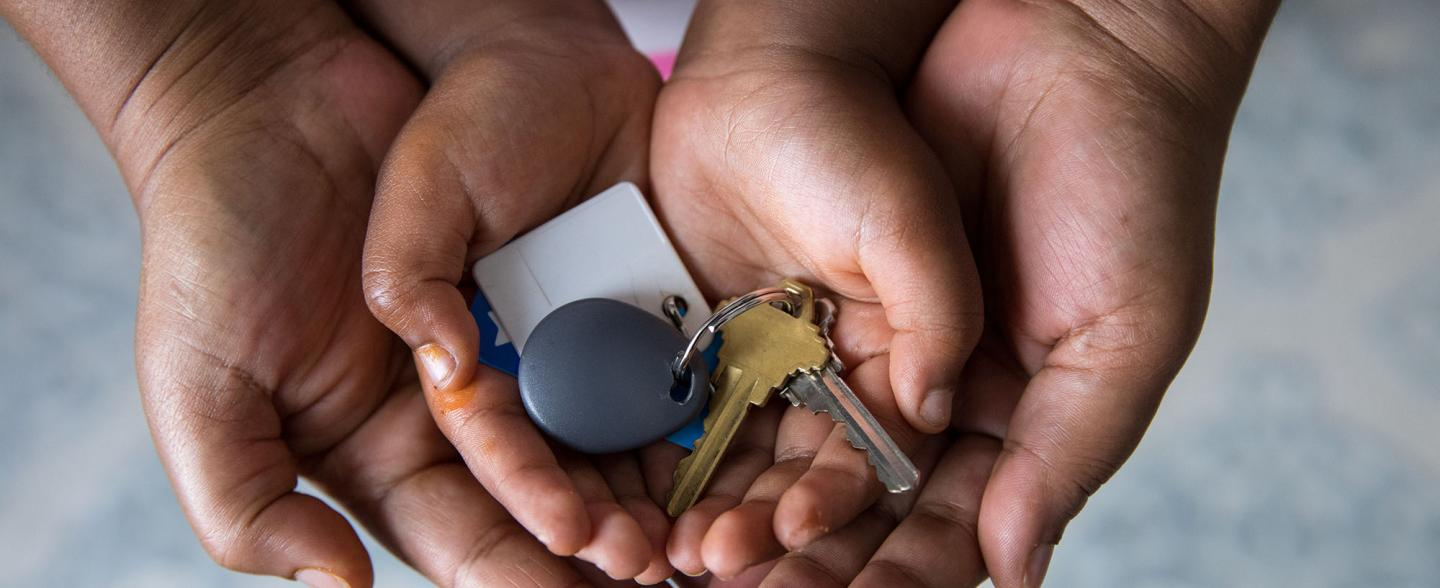 A Black mother's hands cradle child hands with house keys