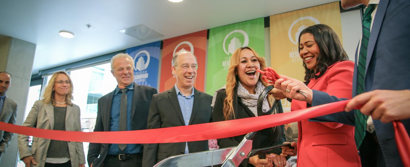 A multi-racial group including Mayor London breed do a ribbon-cutting at 1036 Mission
