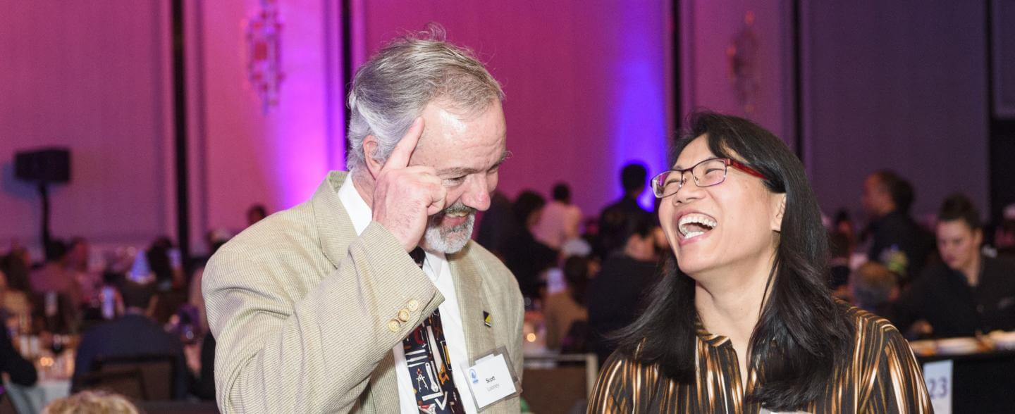 A white man and asian woman are mid-laugh at a gala