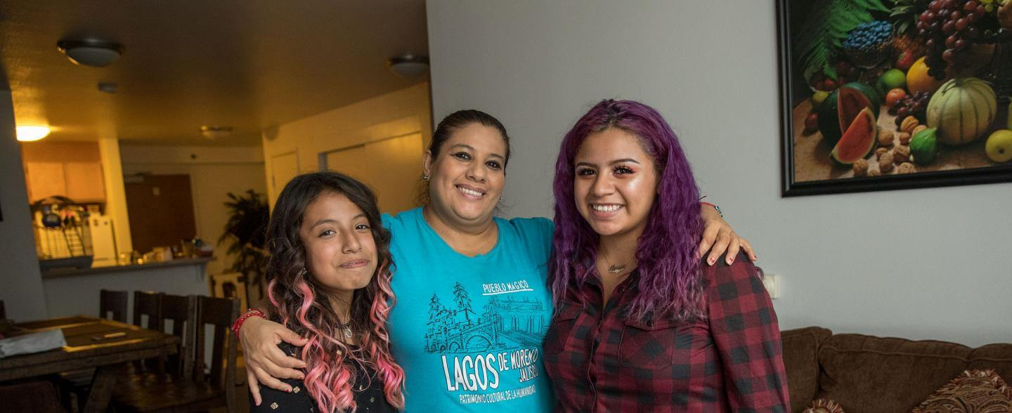 a latinx mom and her two daughters smile in their home