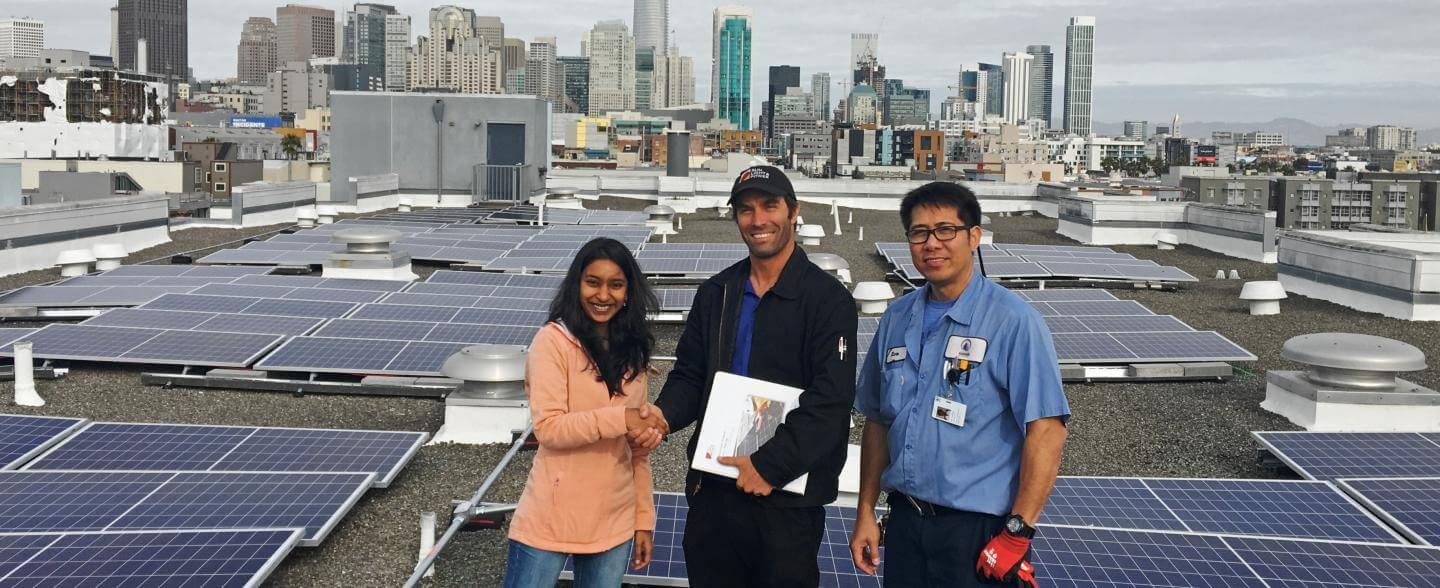 A multi-racial group pose on a rooftop with solar panels