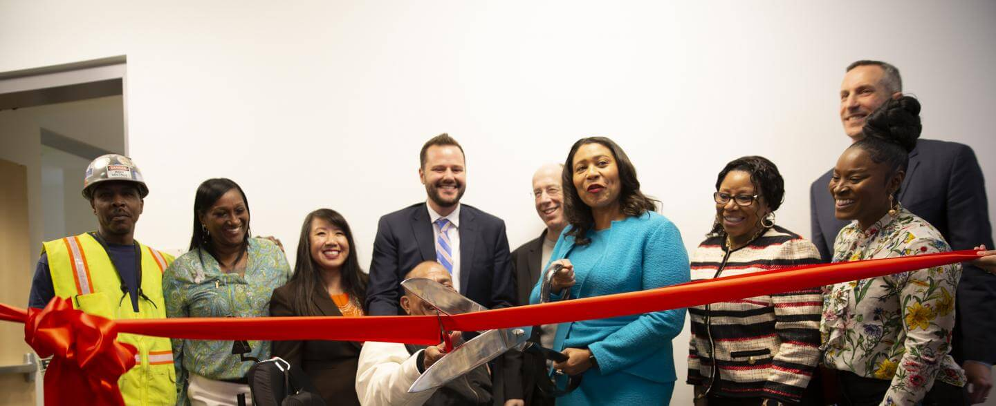 A multi-racial group including Mayor London Breed cut a red ribbon