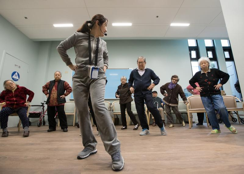 A group of Asian seniors practice Tai Chi