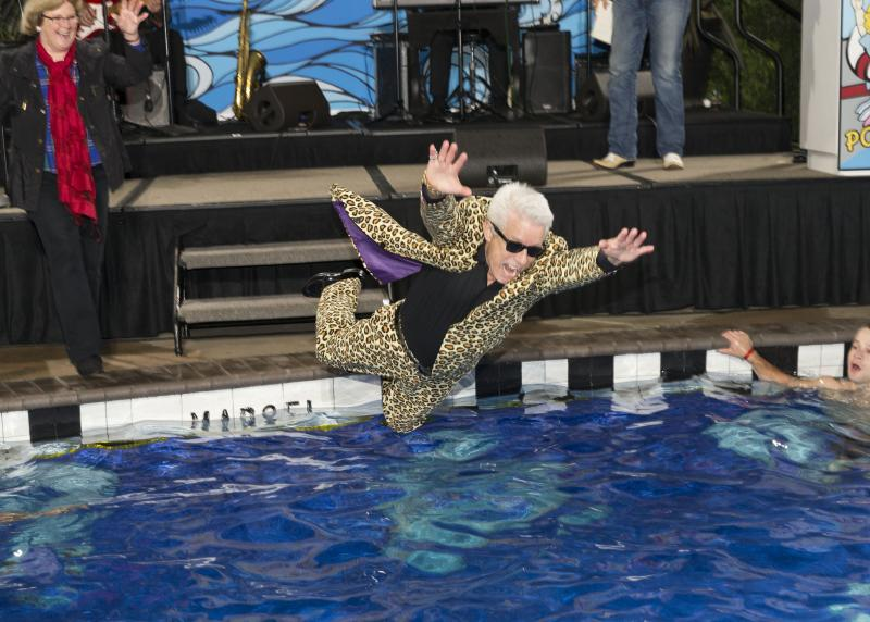 A white man in a cheetah suit flies over a pool