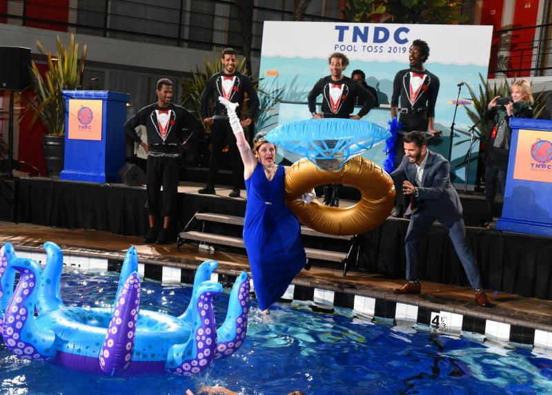 A white woman in a blue gown excitedly jumps into a pool