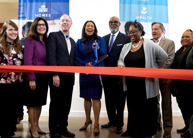 A multi-racial group including Mayor London Breed pose and cut a red ribbon