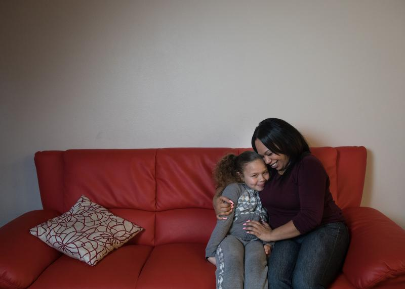 A Black mom happily hugs her child on a red couch