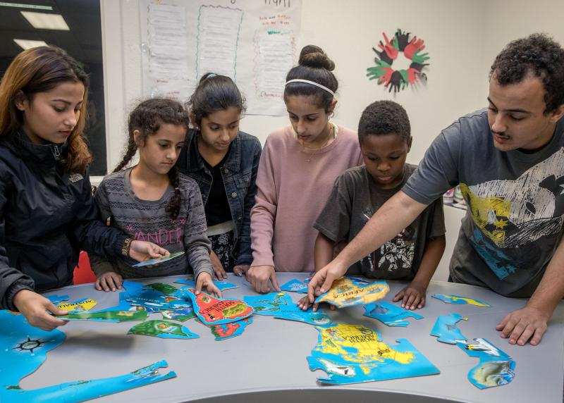 A multi-racial group of kids and teens work on a world map