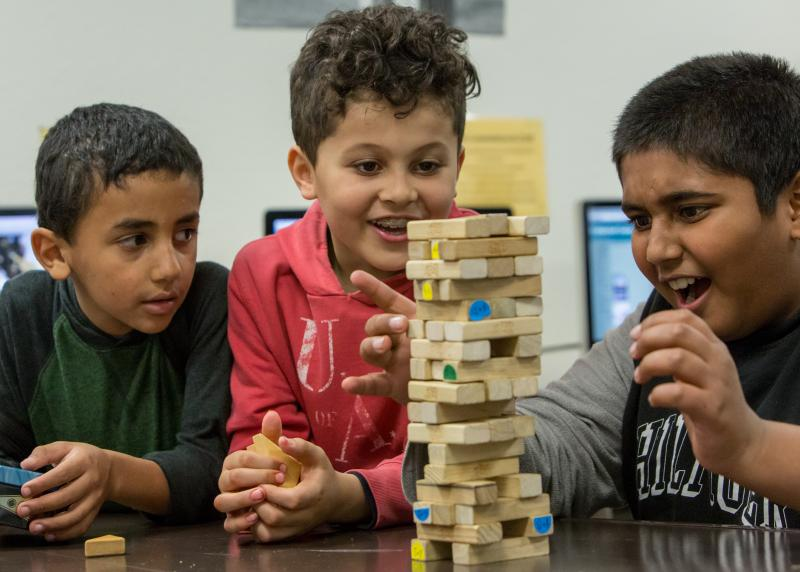 A multi-racial group of young boys excitedly play jenga