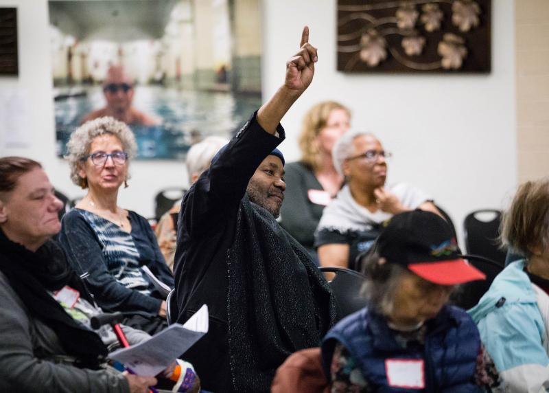A black man raises his hand at a community meeting