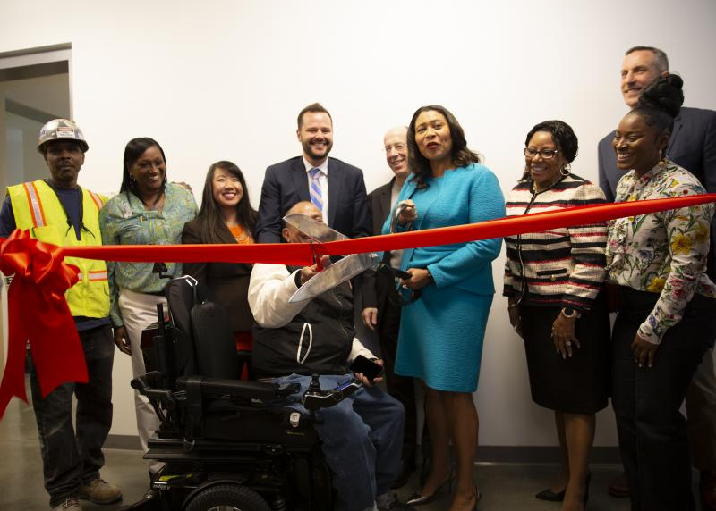 A multi-racial group including Mayor London Breed cut a bright red ribbon