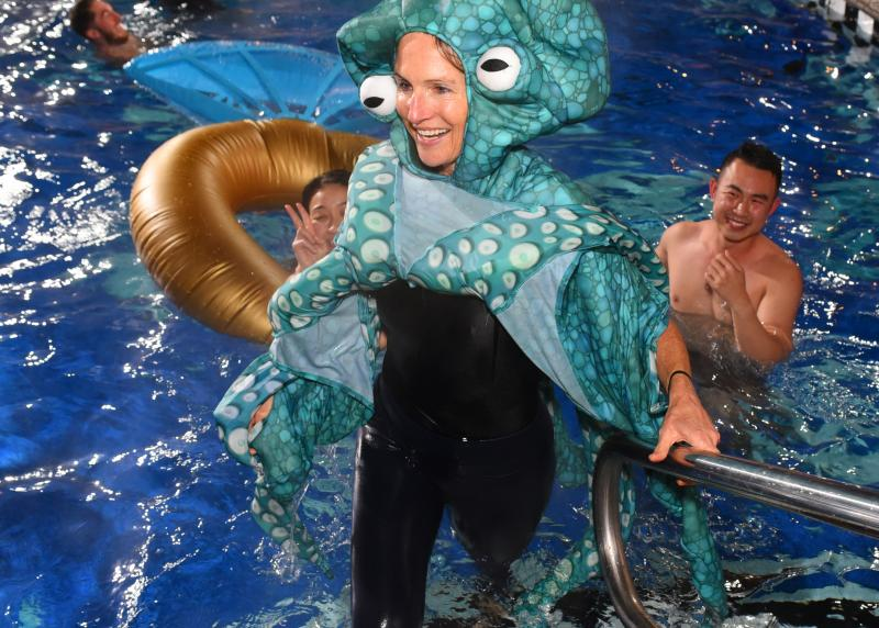 A woman dresses like an octopus gets out of a pool