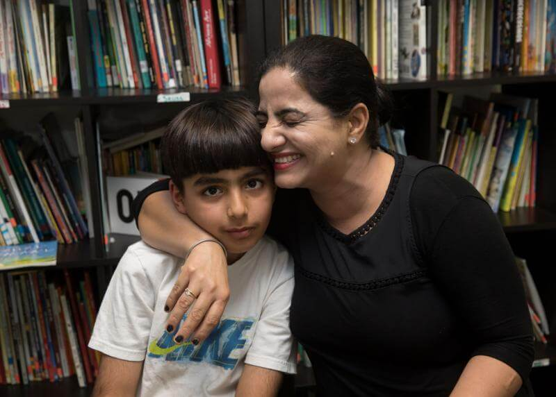 Mom squeezes her son in front of bookshelves