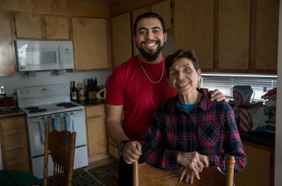 Nicaraguan Grandma and grandson pose together in kitchen